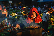 A woman wearing a red towel on her head to keep her cool whilst frying kebabs at the street market, Pak Khlong Talat, Bangkok, Thailand