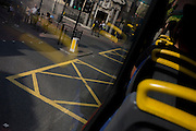 Road box junction and yellow seating handles from the top deck of a double-decker.