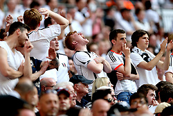 Fulham fans in the crowd react to a missed chance