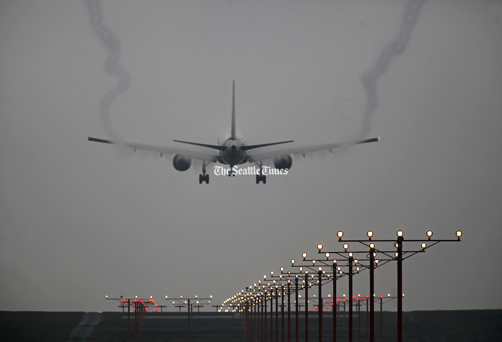 A plane lands at SeaTac International Airport in a day of heavy fog. (Ellen M. Banner / The Seattle Times)