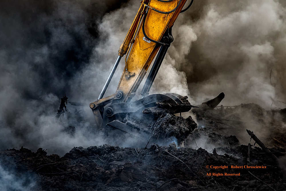 Insatiable: The contrast between nature and the strength of an industrial age is exemplified by this excavators' bucket; as it pauses momentarily amongst the barren ruin and billowing smoke of a farmer's field, Aldergrove British Columbia, Canada.