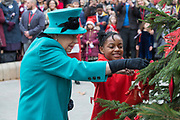 Queen Elizabeth II decorates a Christmas tree with Shylah Gordon-Clarke, aged 8, during a visit to childrens charity Coram to open the Queen Elizabeth II centre on 5th December 2018 in London, England. Coram is the UK's oldest childrens charity and was founded by Thomas Coram.