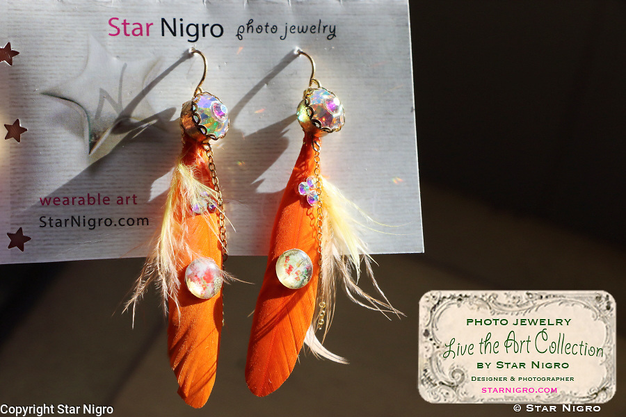 """Flower photo jewelry earrings by Star Nigro<br /> <br /> Materials: orange flower photo, 22K gold accents, orange feathers, swarovski crystals, sterling silver earring hooks<br /> <br /> size: 2"""" x 1/8""""<br /> <br /> price: $64.00<br /> <br /> photo jewelry: Star Nigro<br /> photo by: Star Nigro<br /> model:Palma Latorre artist/fx artist<br /> <br /> gorgeousfrankenfx.wixsite.com/gffx<br /> https://www.facebook.com/GF.effects/<br /> <br /> photo by Star Nigro<br /> <br /> StarNigro.com<br /> <br /> ©2021 All artwork is the property of STAR NIGRO.  Reproduction is strictly prohibited."""
