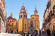 Facade of the Baroque style, Parroquia de Basílica Colegiata de Nuestra Señora de Guanajuato or Guanajuato Basilica in the historic center of Guanajuato City, Guanajuato, Mexico. The massive basilica is painted bright yellow, located in along the Plaza of Peace and was built in 1671.