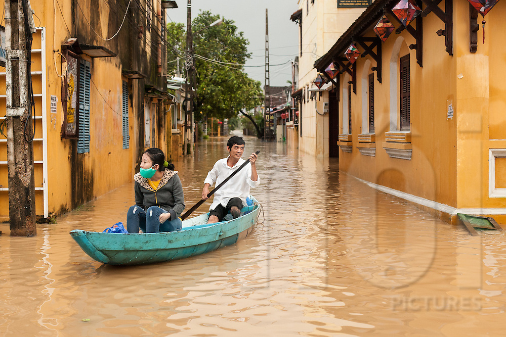 A boat carries passenger during a flood in Hoi An, Vietnam. Southeast Asia