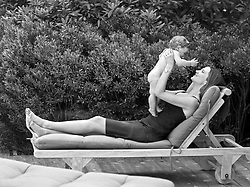 woman holding a baby while on a lounge chair in East Hampton, NY
