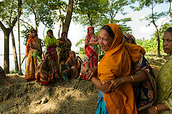 """Women and children from the fishing village of South Tetulbarian in Barguna Sadar upazila  in Bangladesh gather to console Moyna, who just lost her brother in a fishing accident because of violent weather, October 21, 2010 . She was screaming, """"Where is my brother? oh brother, where are you?""""Because of climate change, the seas are getting more violent, less predictable and boats are capsizing more frequently. Twenty percent of the women in this village are widows because so many have lost their husbands in the seas. Coastal and fishing populations are particularly vulnerable and Fishing communities in Bangladesh are subject not only to sea-level rise, but also flooding and increased typhoons. Erosion as a result of stronger and higher tides, cyclones and storm surges is eating away Bangladesh's southern coast.  Yet the largely fishing community cannot live without the sea. """"We only know how to catch fish,"""" say the fishermen. ( Ami Vitale)"""