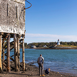 A man and his daughter explore the shoreline in Lubec, Maine. Mullholland Point Light is across Lubec Narrows on Campobello Island.