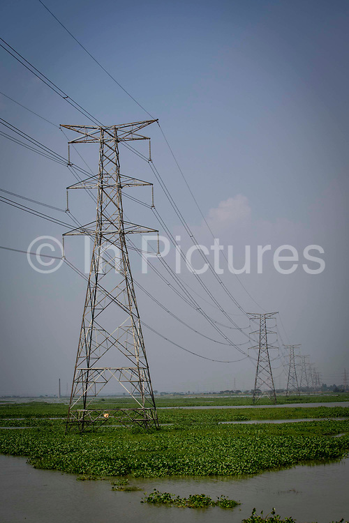 Electricity pylons stand in water on the flood plains next to the Turag river on the 1st of October 2018  in the Ashulia district of Dhaka, Bangladesh.