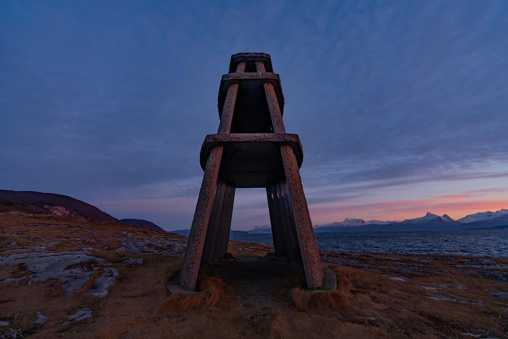 Mørketidslys bak Evenestangen og Steinkirka i Evenes kommune, Nordland. Tøttatoppen og Narvik by kan skimtes bak kirkegangen.