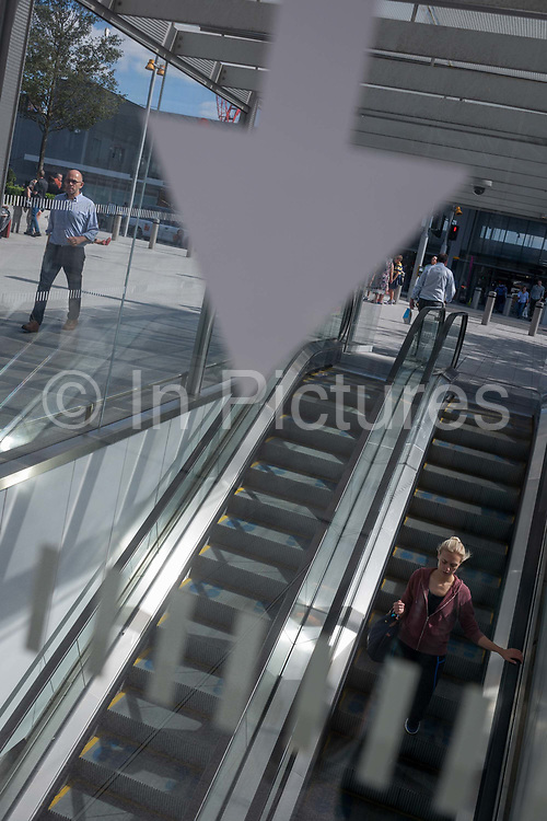 A down arrow and underground travellers who descend by escalator, on 1st September 2016, in Southwark, south London, England UK. As a young woman travels down to the underground station, a man walks at ground level and others are seen on a plaza outside London Bridge.