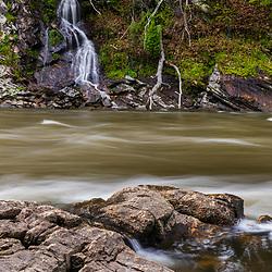 A seasonal waterfalls tumbles down a cliff in the Presumpscot River at Presumpscot Falls in Portland, Maine. Spring.