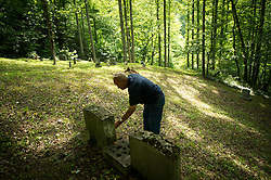 """Near his home in Bandytown, West Virginia, Leo Cook visits the Webb Cemetery, where several of his relatives are buried. Bandytown is in the heart of America, where mountaintop-removal mines are abundant. Mining firms must maintain a 100-foot protective zone around such burial grounds. Mountaintop Removal is a method of surface mining that literally removes the tops of mountains to get to the coal seams beneath. It is the most profitable mining technique available because it is performed quickly, cheaply and comes with hefty economic benefits for the mining companies, most of which are located out of state. Many argue that they have brought wage-paying jobs and modern amenities to Appalachia, but others say they have only demolished an estimated 1.4 million acres of forested hills, buried an estimated 2,000 miles of streams, poisoned drinking water, and wiped whole towns from the map. The mountaintop-removal mine near Blair caused the population to fall from 700 in the 1990s to fewer than 50 today, according to the Blair Mountain Heritage Alliance. """"I saw Lindytown disappear,"""" Leo Cook said. """"Three people up there that died, and I believe in my soul -- I'll go to my grave believin' this?that aggravation's what caused it."""" © Ami Vitale"""