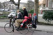 Een man en vrouw fietsen met jonge kinderen achterop door Amsterdam.<br /> <br /> A man and woman are cycling with young childs on the back in Amsterdam