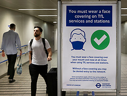© Licensed to London News Pictures. 19/07/2021. London, UK. A poster reminds passengers to wear face coverings as they arrive at King's Cross Underground Station on the morning of Freedom Day. All covid regulations in England are being scrapped from today even though infections and hospitalisations are on the increase. Photo credit: Peter Macdiarmid/LNP