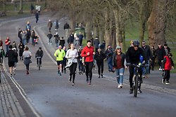 © Licensed to London News Pictures. 17/01/2021. London, UK. Members of the public exercise in a busy Greenwich Park in South East London. A national lockdown is in place in England to attempt to reduce the spread of a new strain of COVID-19 . Photo credit: George Cracknell Wright/LNP