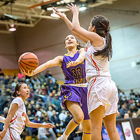 Kirtland Central Bronco Talia Ockerman (33), center, attempts a layup contested by Gallup Bengal Ashley Antone (1)  in the District 1-5A girls tournament at Gallup High School Thursday.
