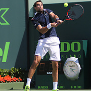 Jeremy Chardy of France attempts to hit the serve of Milos Raonic of Canada during their match at the Miami Open tennis tournament at Crandon Park on Monday, March 30, 2015 in Key Biscayne, Florida. (AP Photo/Alex Menendez)