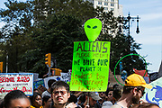 "20 September 2019 - New York, NY.  Thousands of students as well as adults gathered in New York for the Global Climate Strike, meeting in Foley Square near the Federal Government buildings and New York's City Hall, and marching downtown to Battery Park, where Swedish climate activist and spokesperson Greta Thunberg addressed the crowd. Marchers on Broadway carry signs, one of which reads ""Aliens please help! We broke our planet :( leaders too vain, corrupt, to fix :("""