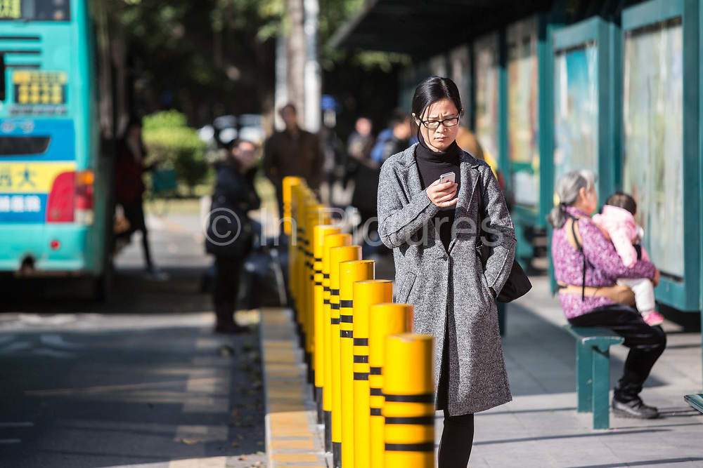 Morning commuters look at their smart phones as they wait for their rides in Shenzhen, China, on Thursday, Dec. 17, 2015.