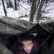 Great Gray Owl, (Strix nebulosa)  7 year old Colter Hyde in tower blind near owl nest with chicks. Montana.