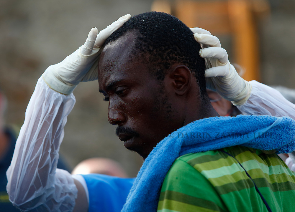 A Sub-Saharan migrant is medically examined by an Italian health official after disembarking from the Migrant Offshore Aid Station (MOAS) ship MV Phoenix in Vibo Valentia, Italy, July 31, 2015.  195 migrants who were rescued off Libya on Wednesday arrived in Italy on Friday afternoon. The Phoenix, manned by personnel from international non-governmental organisations Medecins san Frontiere (MSF) and MOAS, is the first privately funded vessel to operate in the Mediterranean.<br /> REUTERS/Darrin Zammit Lupi <br /> MALTA OUT. NO COMMERCIAL OR EDITORIAL SALES IN MALTA