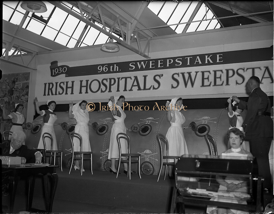 28/05/1959<br /> 05/28/1959<br /> 28 May 1959<br /> Irish Hospitals Trust 96th Sweepstake Draw on the 1959 Derby at Irish Hospital Sweepstakes office, Ballsbridge, Dublin. Picture shows the nurses standing by the drum while a Garda Superintendent takes a drawn ticket from them. In front is the smaller drum with the names of the horses.