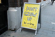 Amusing age related board outside a coffee shop in the City of London on 26th May 2021 in London, United Kingdom. The board reads Dont grow up, its a trap.