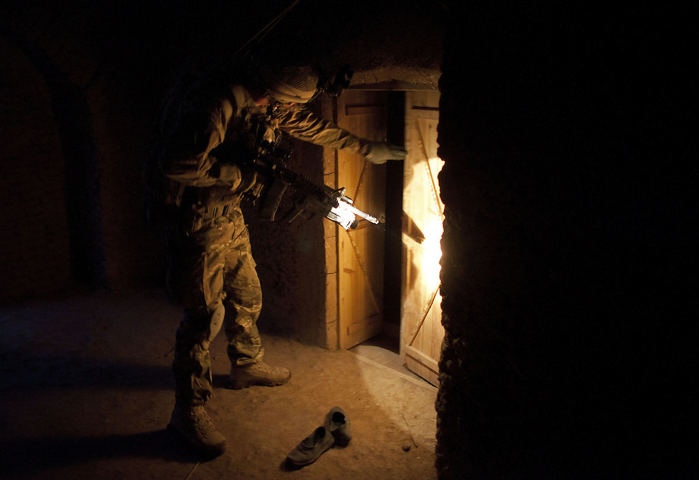 A British soldier of 16 Air Assault Bde's elite BRF (Brigade Reconnaissance Force) searches a compound for weapons and explosives during a dawn raid as part of an operation in the Western Dasht, Helmand Province, Southern Afghanistan on the 20th of March 2011.