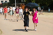 Tourists with a sun umbrella and ice cream walking through St Jamess Park in London, England during sunny weather in the ongoing summer heatwave on August 07, 2018.
