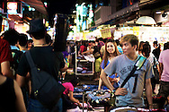 Vendors in Taipei, Taiwan's Shilin Night Market react to a man walking with an old school boom box.  Taiwan's night markets are famous places to find everything from clothes to food to video games and other entertainment.  Every neighborhood in Taiwan has one, and they're the place to be on a Friday or Saturday night.