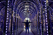 A visitor to the Covent Garden area of the West End, stretches out his arms inside a multi-changing coloured archway off Long Acre, on 22nd January 2019, in London England.