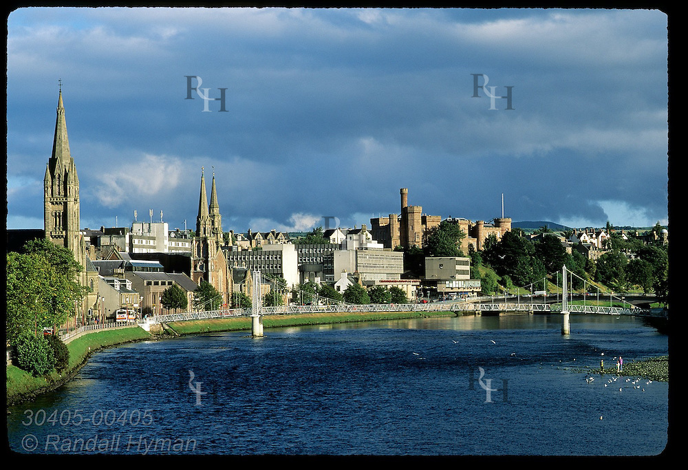 View from Friar's Bridge of footbridge, Old High Church, Inverness Castle and the River Ness in the center of Inverness, Scotland.