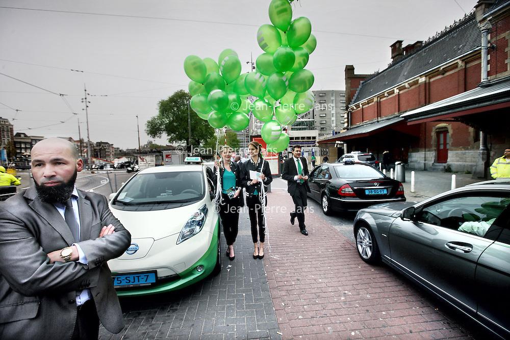 Nederland, Amsterdam , 1 juni 2013.<br /> Presentatie nieuwe taxiregels bij Centraal station voor taxichauffeurs in Amsterdam.<br /> Vanaf a.s. zaterdag worden de nieuwe taxiregels in Amsterdam gehandhaafd. Die komen erop neer dat elke chauffeur moet zijn aangesloten bij een taxionderneming-met-vergunning. Het aantal toegelaten chauffeurs daalt daardoor van zo'n 4000 tot 2300, en het is uiteraard de bedoeling dat zo vooral de slechtsten geweerd worden.<br /> Het handhaven start officieel om acht uur 's ochtends bij het Centraal Station - waar, samen met het Leidseplein, de chaos altijd het grootst is. Daar zullen alle betrokkenen (onder meer de burgemeester en taxidirecteuren) aanwezig zijn.<br /> Opvallend was de aanwezigheid van het milieu bewuste taxi bedrijf Taxi-electric die mooie jonge dames met groene ballonnen liet rondlopen tijdens de presentatie op het Centraal Station.<br /> Niet iedere aanwezige taxi chauffeur kijkt even blij.<br /> Foto:Jean-Pierre Jans