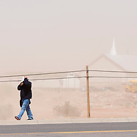 040813       Brian Leddy<br /> A man covers his head from the wind and dust while walking along Highway 264 in Window Rock Monday afternoon. The wind storm brought 60mph gust along with dust and bouts of rain.