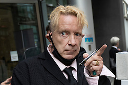 © Licensed to London News Pictures. 21/07/2021. London, UK.  John Lydon, former frontman of iconic punk band The Sex Pistols, once known as Johnny Rotten, signs autographs as he leaves the High Court Rolls building in central London.  Bandmates Paul Cook and Steve Jones are suing Lydon over the use of their songs in a new Danny Boyle film. Mr Lydon is arguing that licences for the songs cannot be given without his consent. Photo credit: Peter Macdiarmid/LNP