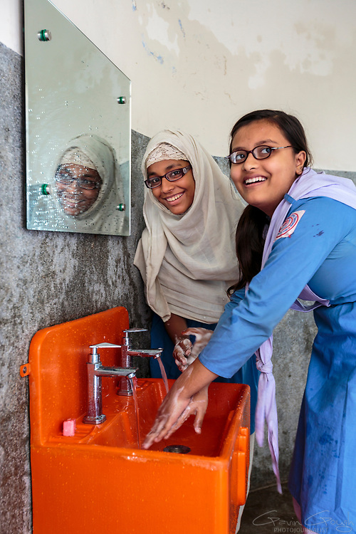 Two schoolgirls washing their hands with clean water in a Splash sink
