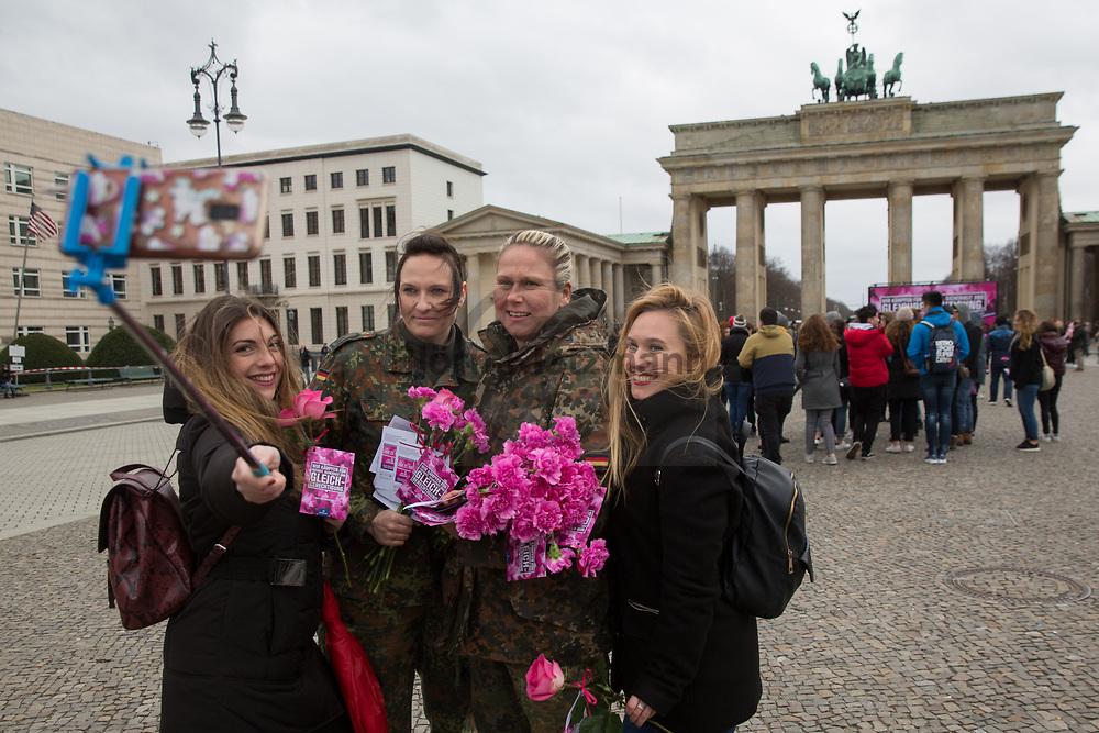Berlin, Germany - 08.03.2019 <br /> <br /> Female German soldiers distribute flowers to women at the Brandenburg Gate on the occasion of International Women's Day and to promote the profession of soldiers.<br /> <br /> Bundeswehrsoldatinnen verteilen am Brandenburger Tor Blumen an Frauen anlaesslich des internationalen Frauentags und um fuer den Soldatenberuf zu werben.<br /> <br /> Photo: Bjoern Kietzmann