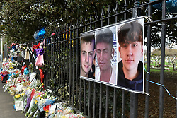 © Licensed to London News Pictures. 29/01/2018. London, UK.  Photographs hang on railings above floral tributes.  (L to R) George Wilkinson, 16, Harry Rice, 17, and Josh Mcgunnies, 16, were killed when a car mounted the pavement in Hayes, west London, on the night of 27 January. Jaynesh Chudasama, 28, of Hayes has been charged with three counts of causing death by dangerous driving and will appear in custody at Uxbridge Magistrates Court on Monday 29 January.  Photo credit: Stephen Chung/LNP