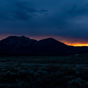 Late afternoon thunderstorms leave a colorful series of clouds behind Mammoth Mountain as the sun dips below the horizon.