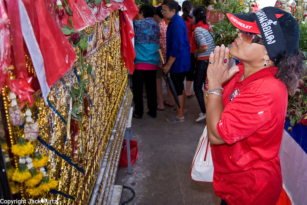 Apr. 14 - Bangkok, Thailand: A woman prays and pays respects at the coffins of Red Shirts who died in street fighting Saturday. The bodies of the Red Shirts who died during Saturday's fighting are lying in repose at Democracy Monument. Thousands of Thais have filed past to show their respect. The Red Shirts moved their main protest its original location in the old part of Bangkok to the Ratchaprasong intersection, in the center of Bangkok's shopping malls and five star hotels. Many signs of last weekend's violence is still on display around their original encampment though. Photo by Jack Kurtz