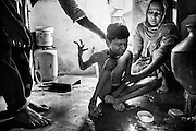 Saba, 31, a '1984 Gas Survivor', is being helped by her husband (left) when washing their disabled son Aman Qureshi, 14, a boy affected by severe cerebral palsy, while sitting inside their bathroom in Aishbag Colony, Bhopal, Madhya Pradesh, central India.