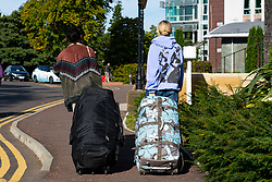 Edinburgh, Scotland, UK. 27 September, 2020.   Two female students with luggage leave  Pollock Halls by taxi. Pollock Halls is one of Edinburgh University's halls of residence. Following local outbreaks of Covid-19 amongst students at Scottish universities many have had to self-isolate in their rooms. Over the weekend students have been seen leaving campuses often being picked up by parents. Iain Masterton/Alamy Live News