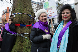 London, UK. 12th January, 2018. Coral Bower (c) and Mimi Romilly (r) pose with an anti-HS2 placard in Euston Square Gardens. Local residents and environmental campaigners are protesting against the planned felling of mature London Plane, Red Oak, Common Whitebeam, Common Lime and Wild Service trees in Euston Square Gardens to make way for temporary sites for construction vehicles and a displaced taxi rank as part of preparations for the HS2 high-speed rail line.