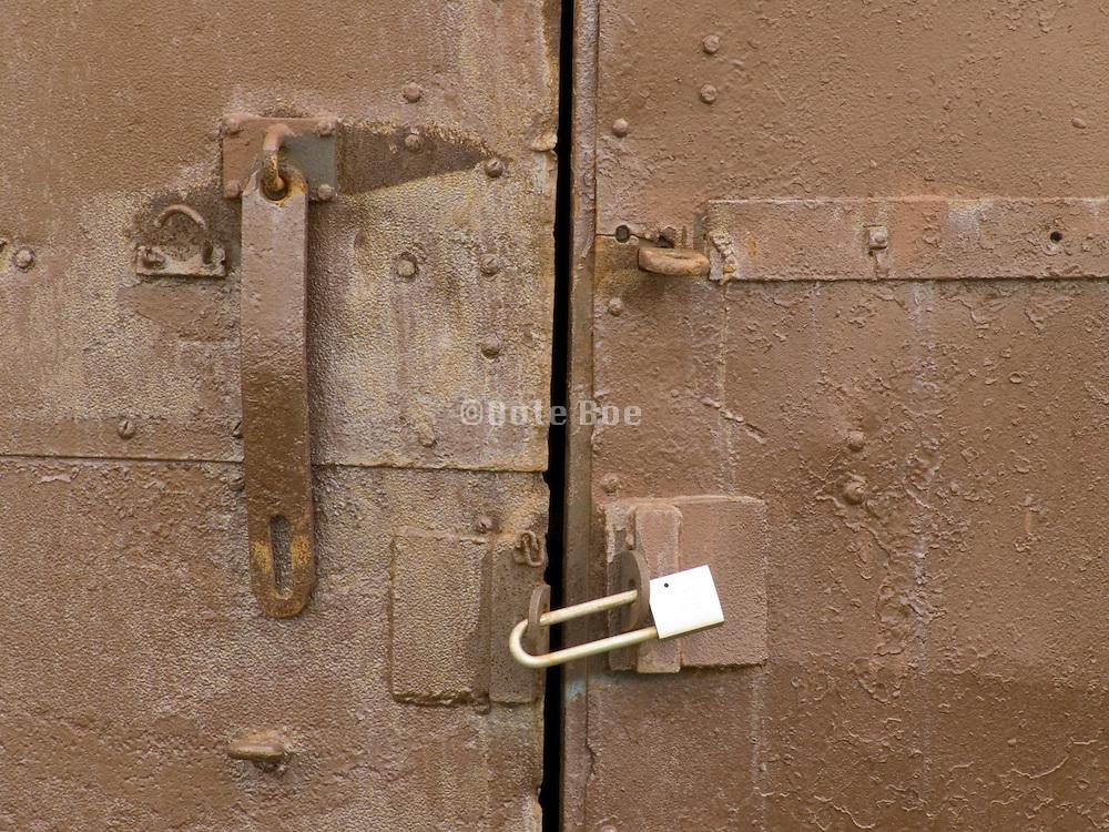 Close up of an old metal door locked with a padlock