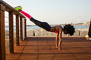 happy young african woman stretching and warming up before an outdoor workout. The Mediterranean sea in the background