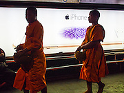 23 NOVEMBER 2014 - BANGKOK, THAILAND: Buddhist novices (young monks) at a mass alms giving ceremony in Bangkok Sunday. 10,000 Buddhist monks participated in the ceremony on Rajadamri Road in front of Central World shopping mall. The alms giving was to assist Buddhist temples in the insurgency wracked southern provinces of Thailand, where Buddhist monks on their alms rounds have been targeted by Muslim extremists. The ceremony was sponsored by Wat Phra Dhammakaya, the center of the Dhammakaya Movement, a Buddhist sect founded in the 1970s. The temple has become active in Thai politics.    PHOTO BY JACK KURTZ