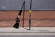 Man walks past leaning post and its own shadow on a brick wall in south London.