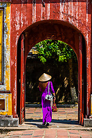 A Vietnamese woman wearing Ao dai, the traditional women's costume walks through an ornate gate in the Imperial City, a walled palace within the citadel of the city of Huế which is the former imperial capital of Vietnam. Hue, Central Vietnam.