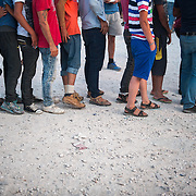 Refugees and immigrants waiting in the queue to receive their supper, a small portion of rice with beans at Kara Tepe camp in Lesbos.